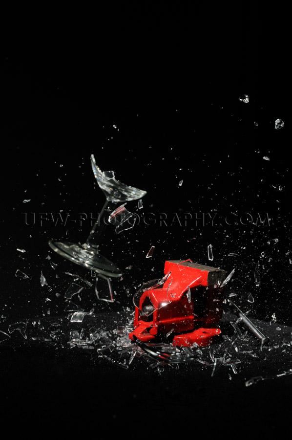 Glass breaking exploding red bench vise black background Stock I