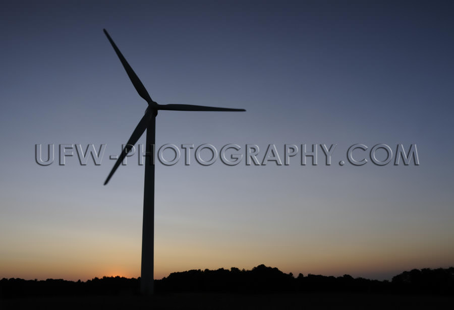 Black wind turbine silhouette, dark blue and orange night sky -