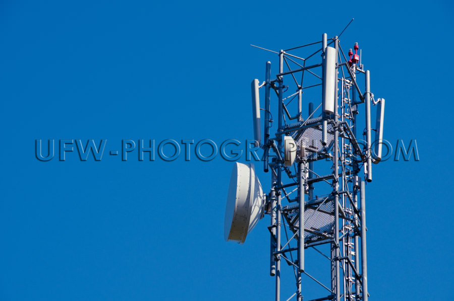 Mobile phone antenna close up against deep blue clear sky Stock