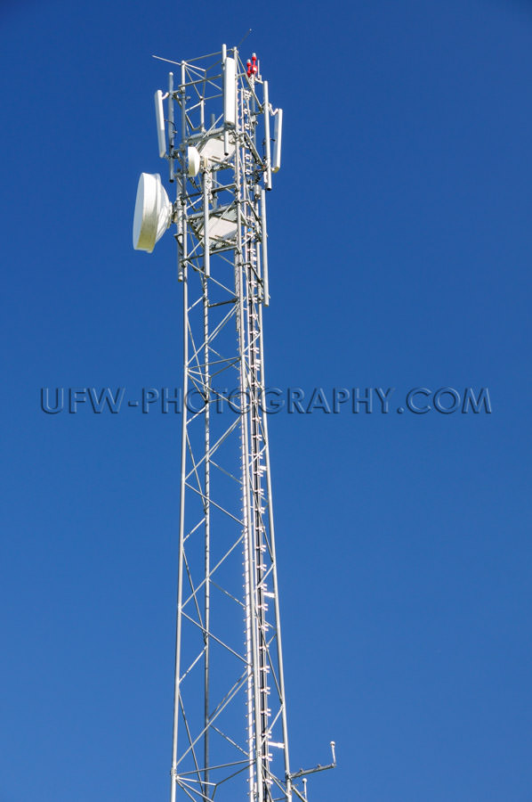 Mobile phone antenna transmitter dish deep blue clear sky Stock