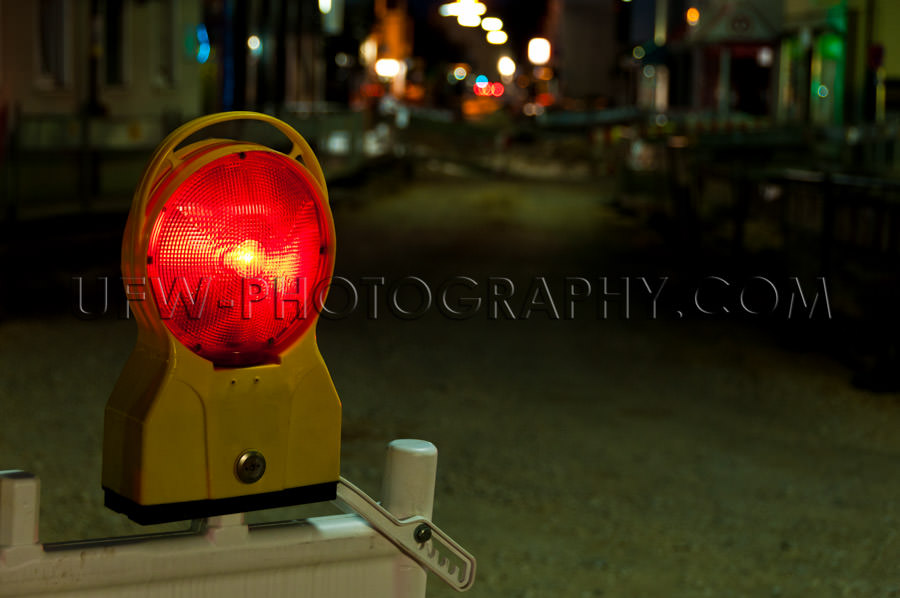 Red warning light illuminated road construction site night Stock
