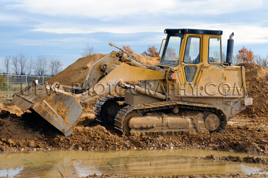 Track loader dirty bulldozer caterpillar tracks mud puddle Stock