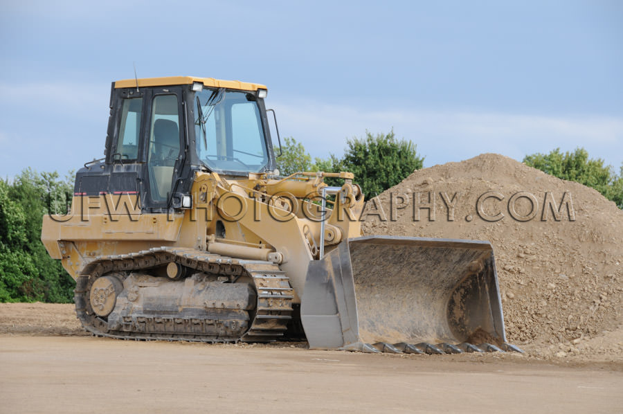 Yellow bulldozer with caterpillar tracks, dirt heap, full frame