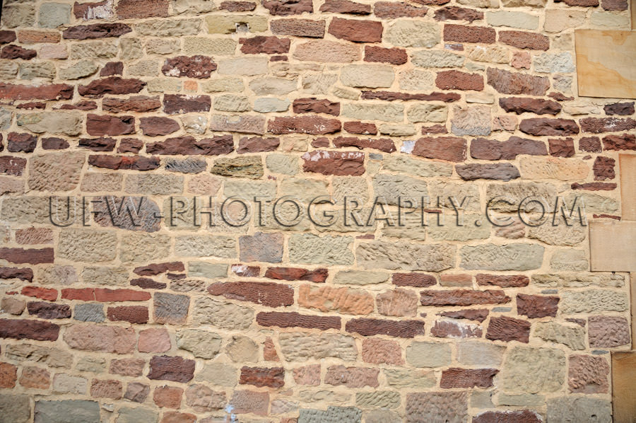 Crude stone wall colored ancient building Background Stock Image