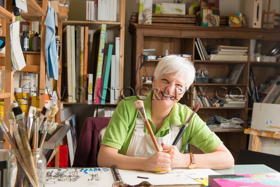 Ältere Künstlerin Mit Zwei Pinseln Atelier Stock Foto