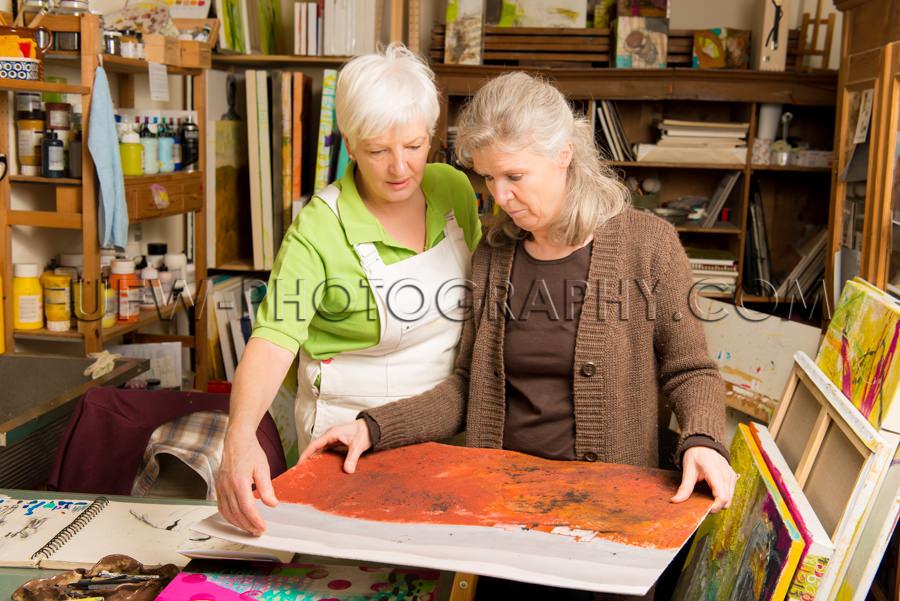 Ältere Künstlerin Reden Mit Frau Zeigen Gemälde Stock Foto