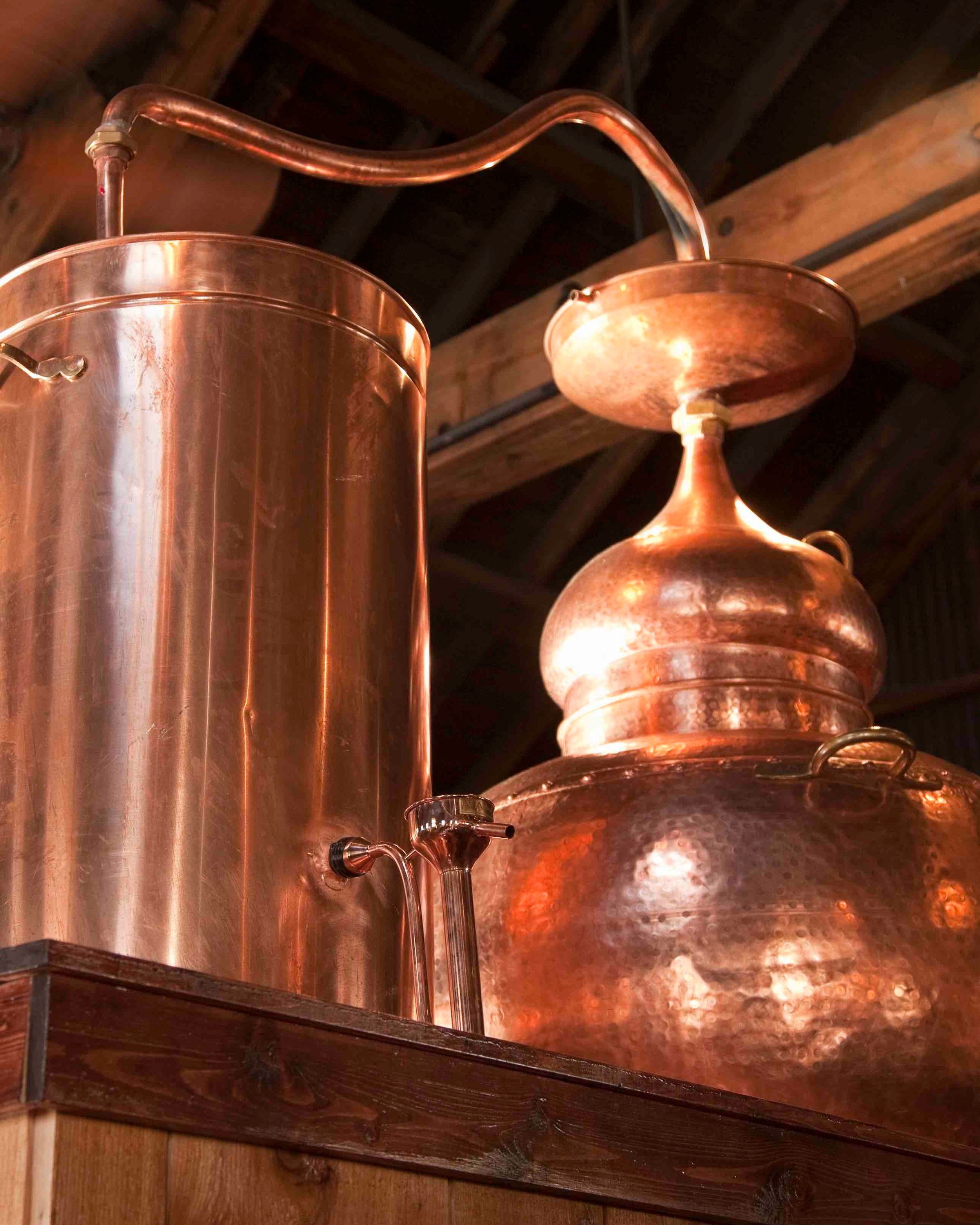 Key Parts of the Rum Still - The lentil. This unique shape at the top of the still (top right, below the copper tube) hides an inside channel that forces steam to flow upward in a spiral, while cold water runs across the top. This creates precise and consistent reflux.The swan's neck. This curved copper tube (at the top of the photo) carries the steam across to the condenser, where it is cooled.The condenser. This tank (on the left of the picture) is filled with a steady stream of cold water, turning hot steam into cool liquid high-proof rum.