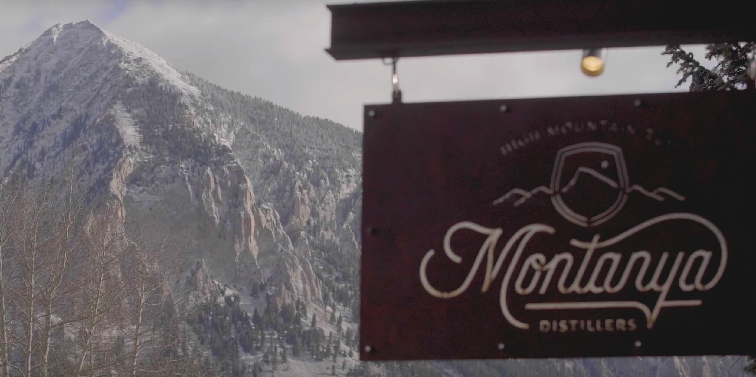Montanya Distillers sign in front of Crested Butte Mountain Peak.