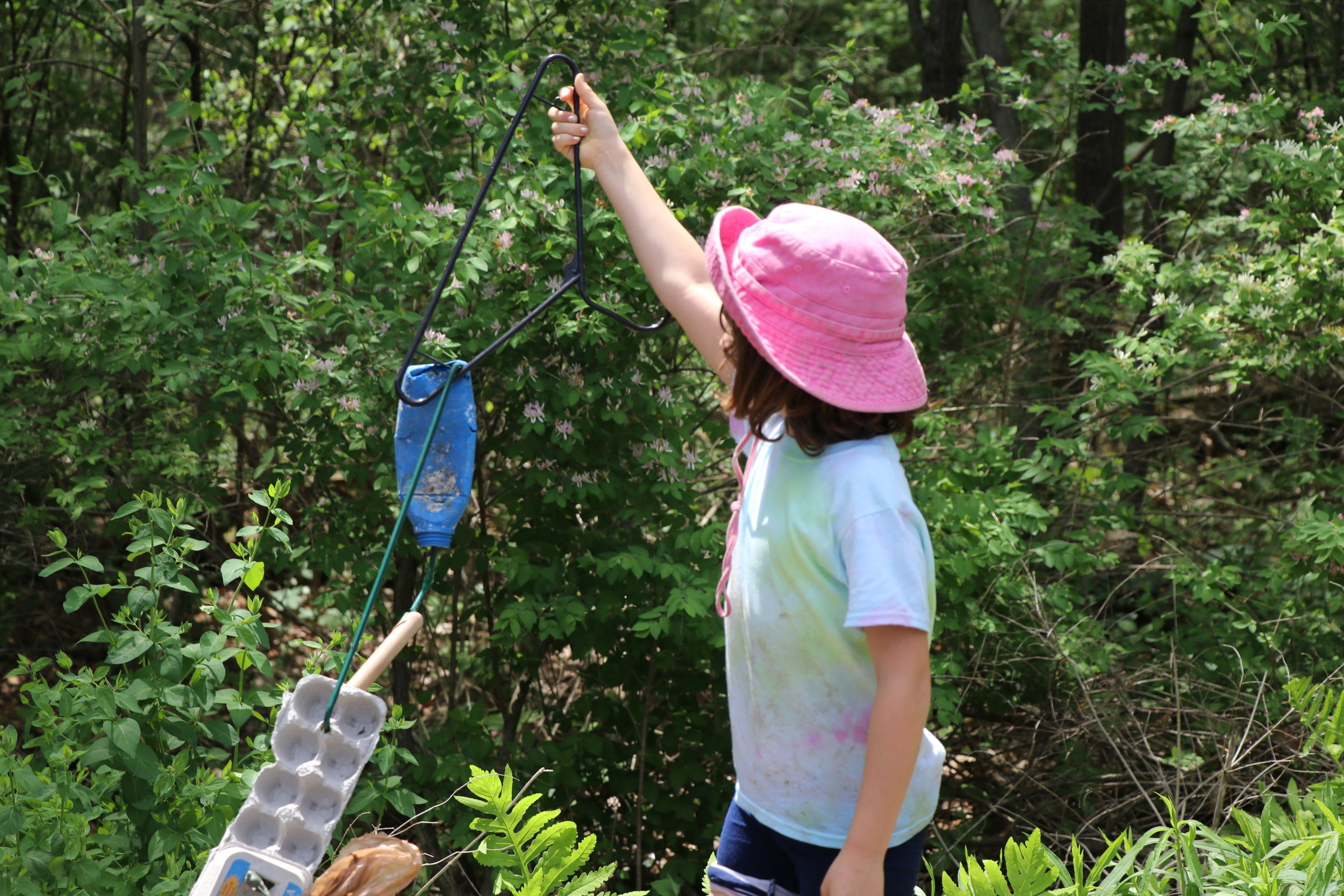 """Child inspecting plastic """"trash art"""" at a workshop I led in Poughkeepsie, NY. May 2016."""