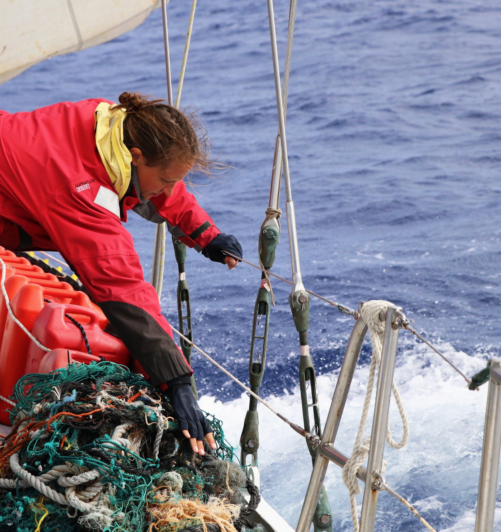 Photo: Scientist Malene Møhl secures ghost net on deck of S/Y Christianshavn in the North Pacific Gyre, 2016. ©Erica Cirino
