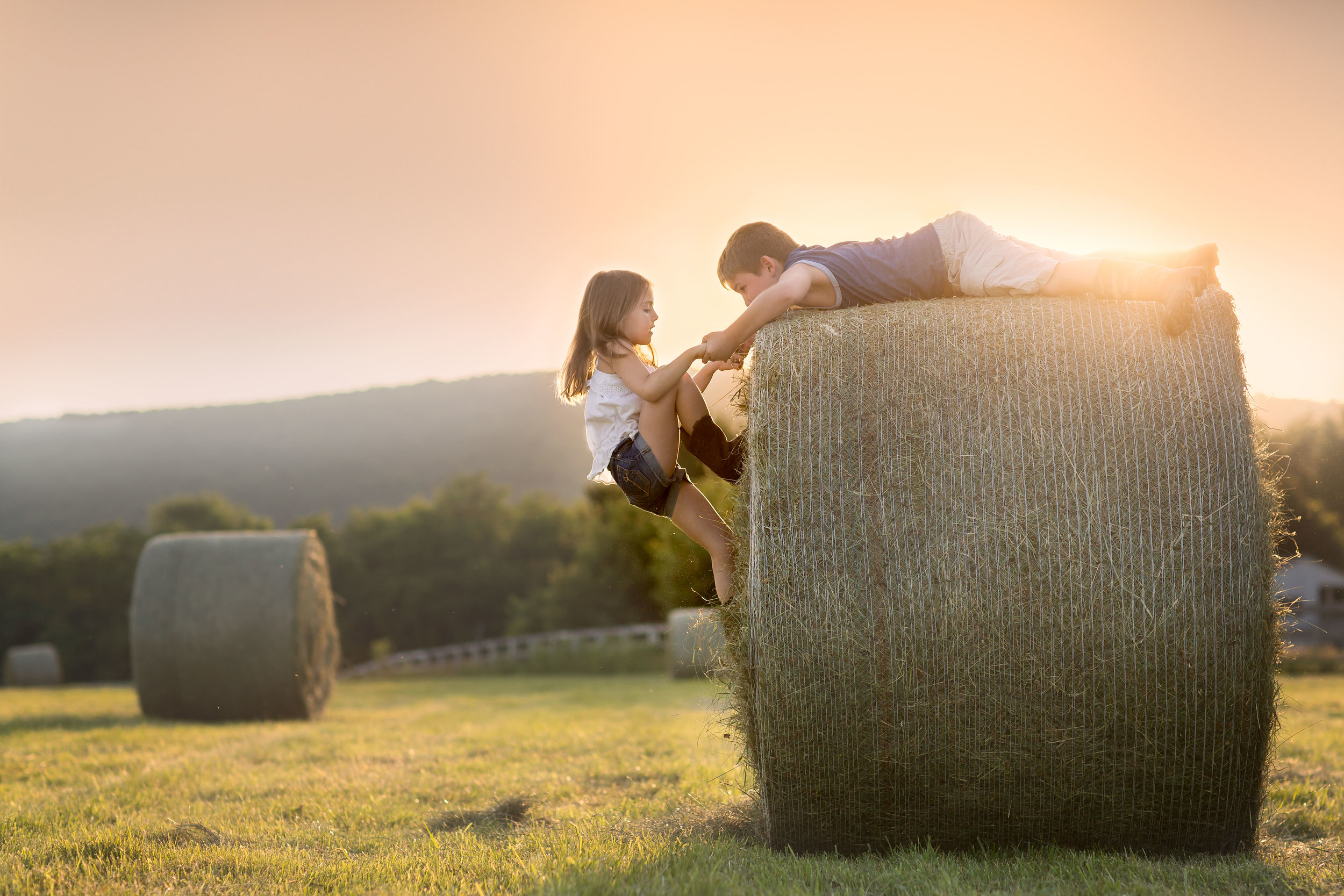 Photography of Children playing on hay bales in Frederick MD by Clare Ahalt Photography , a fine art photographer located in Frederick, MD specializing in child photography, senior portrait photographer and pet portraiture.