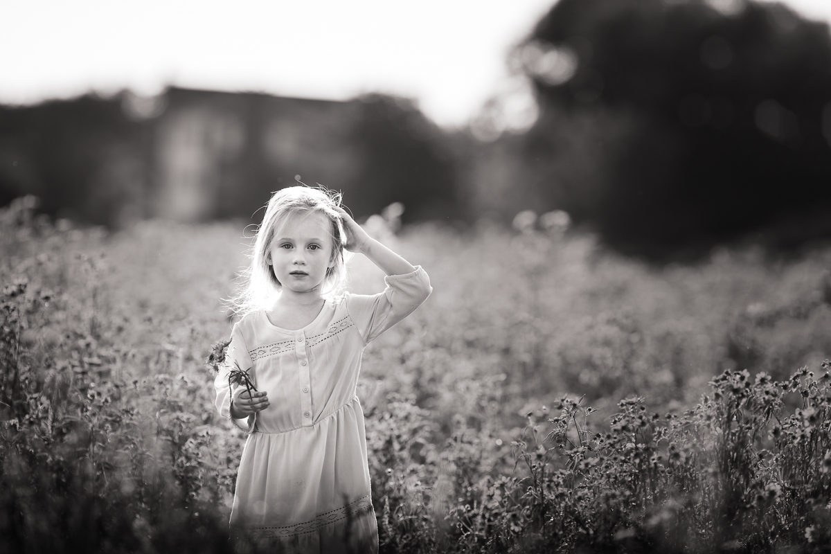 Black and white photographic portrait of a little girl stood in a field of wildflowers.  Photographed by Clare Ahalt Photography, a fine art portrait photographer located in Maryland, serving Maryland, Northern Virginia, Washington DC and Greater Baltimore.  Photographed at a workshop held by Elena Shumilova Photography, photographed on location in Northern Virginia