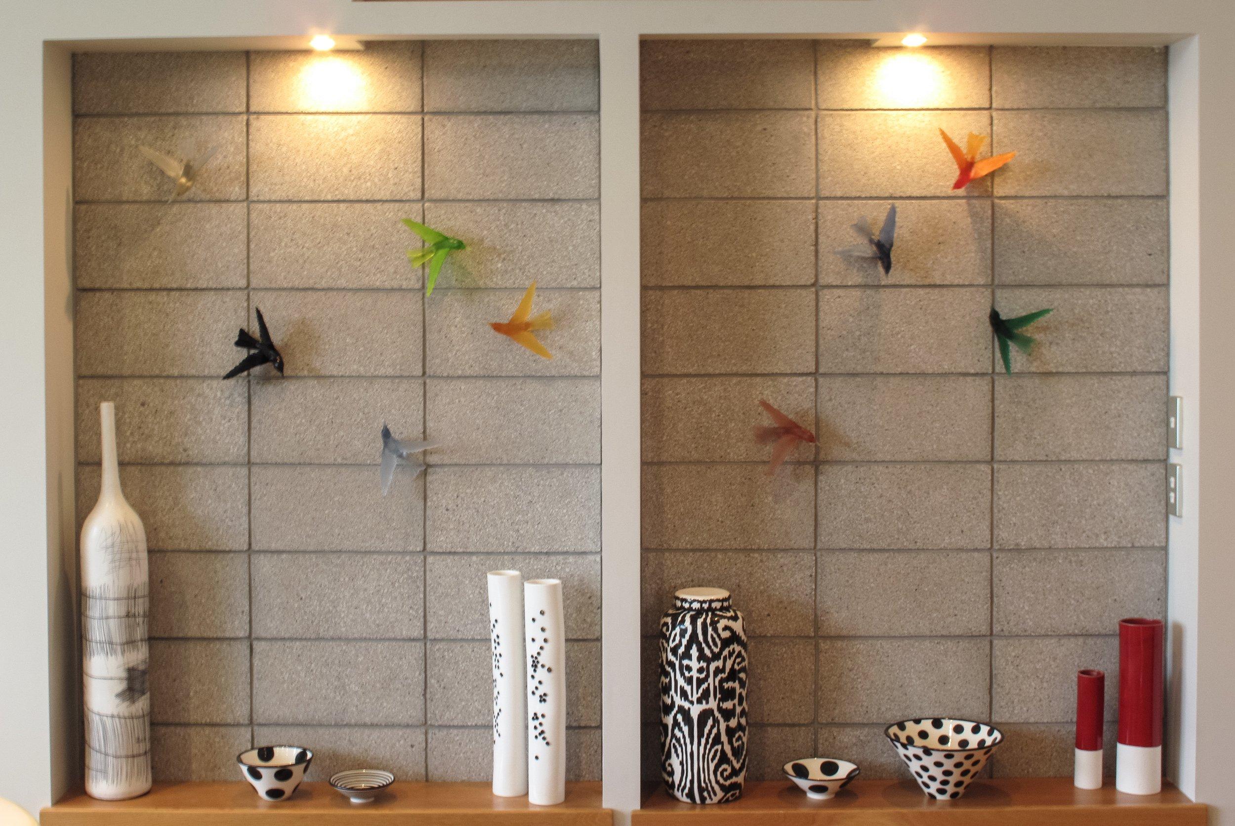 cast glass birds on block wall