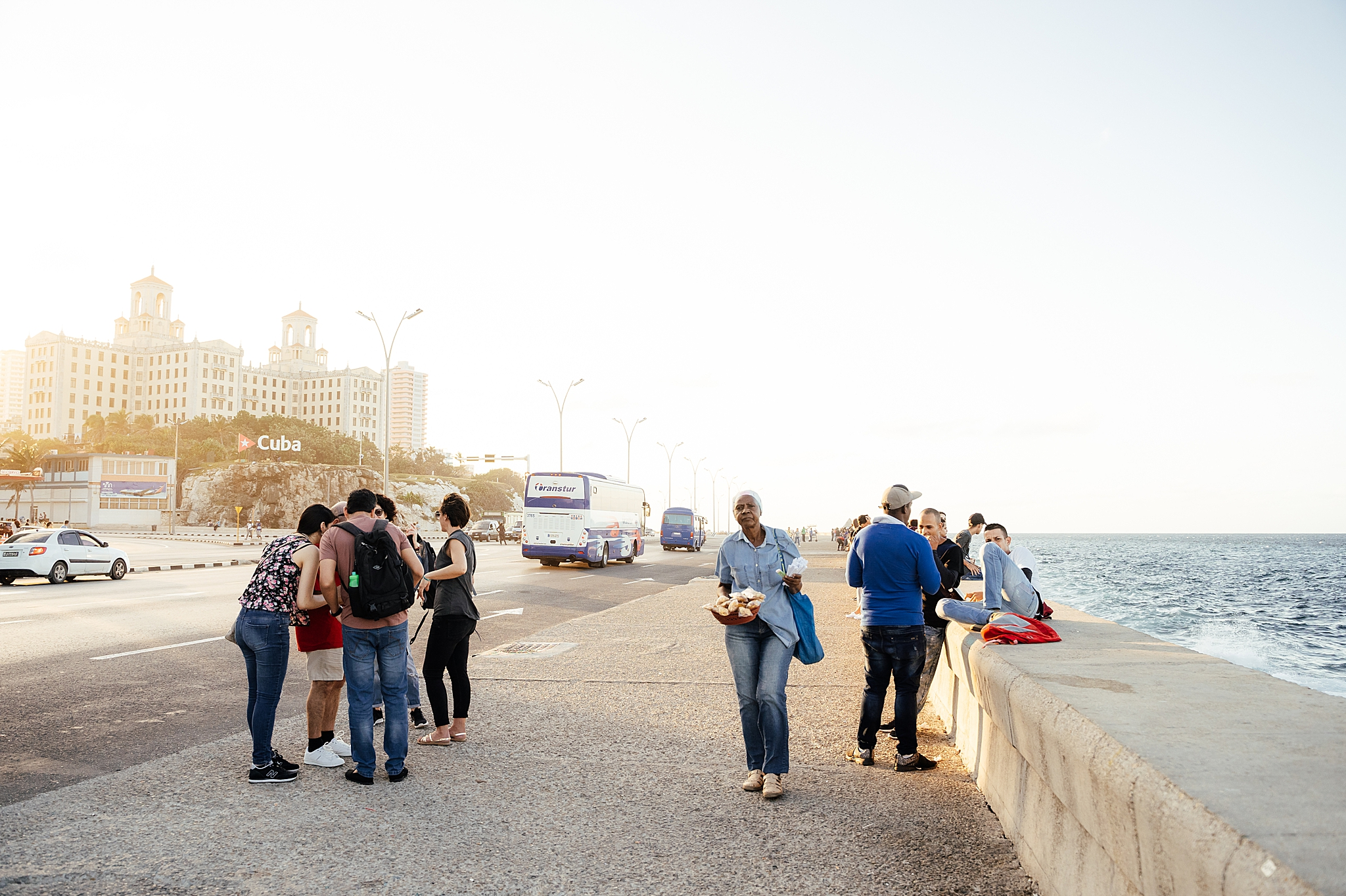 People walking the malecon at sunset in Havana Cuba.
