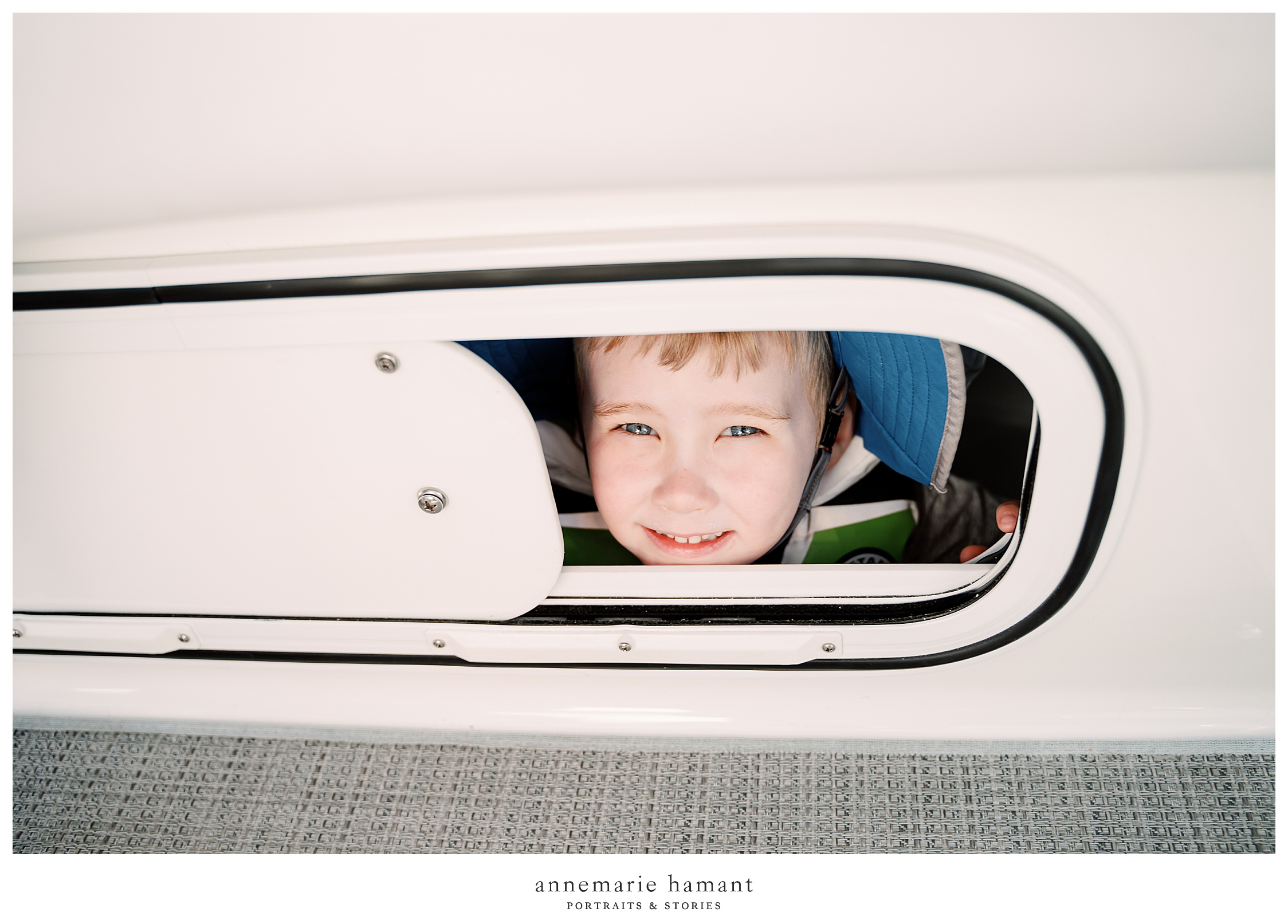 Child peeks through porthole on boat ride.