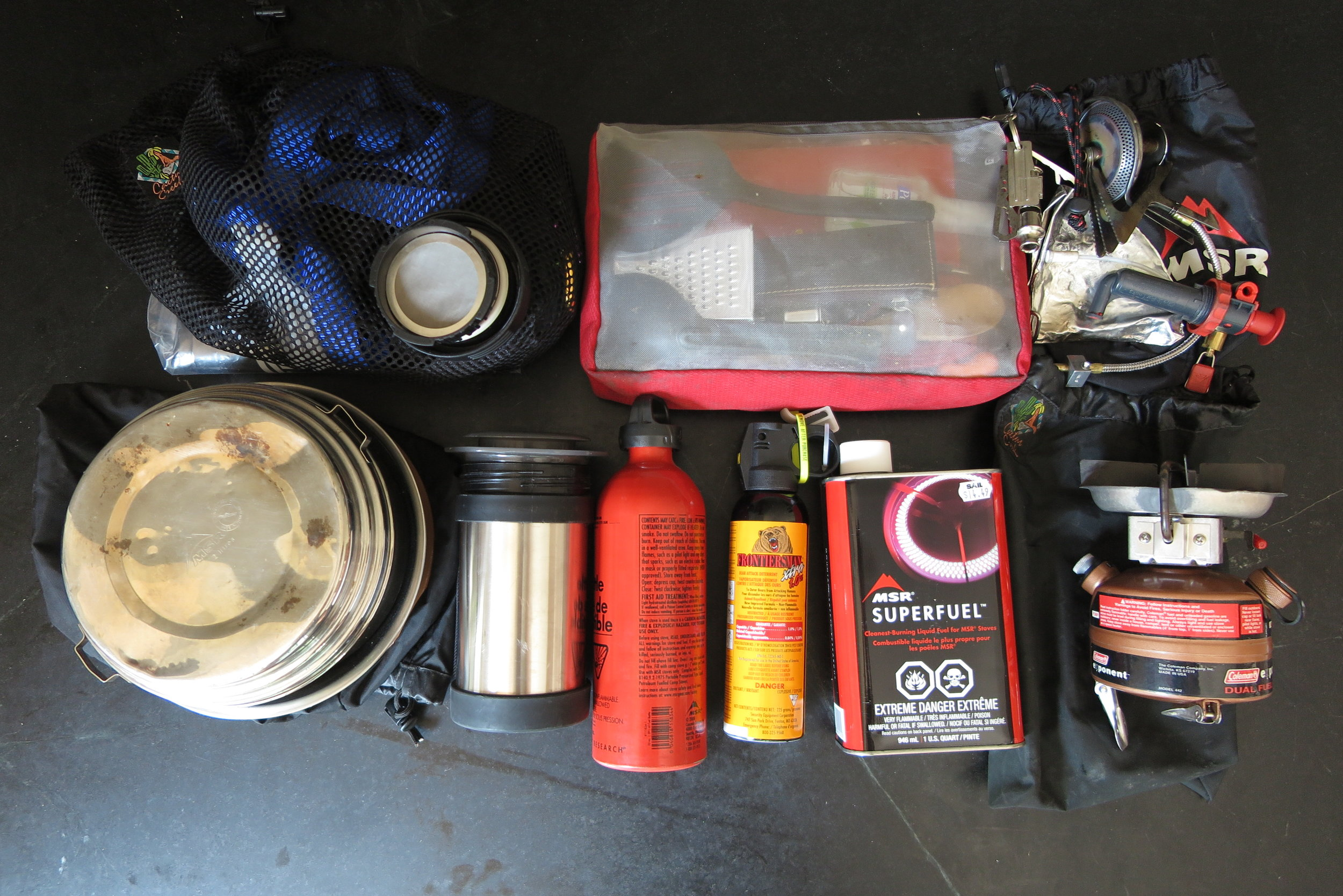 Right Pannier - Fuel can and bottle, coleman and whisperlite stove, kitchen utensils, aeropress coffee maker in mug, bear spray, potset, fry pan, bowl and small mesh bag of ropes, straps, zipties, etc.