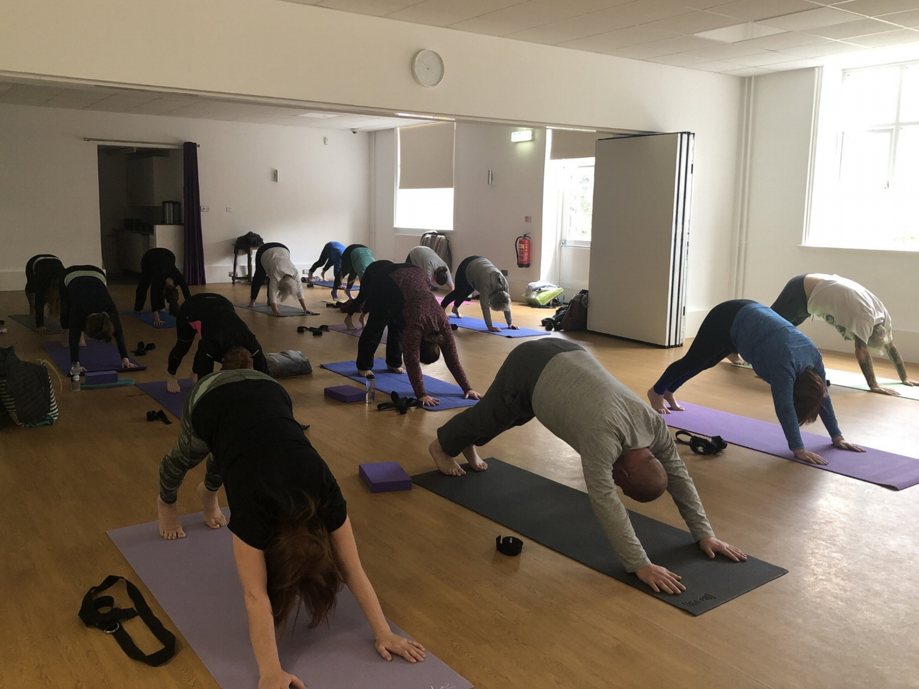 The yoginis and yogis of John Godber Centre, Hucknall Nottingham strengthening their shoulders in downward facing dog