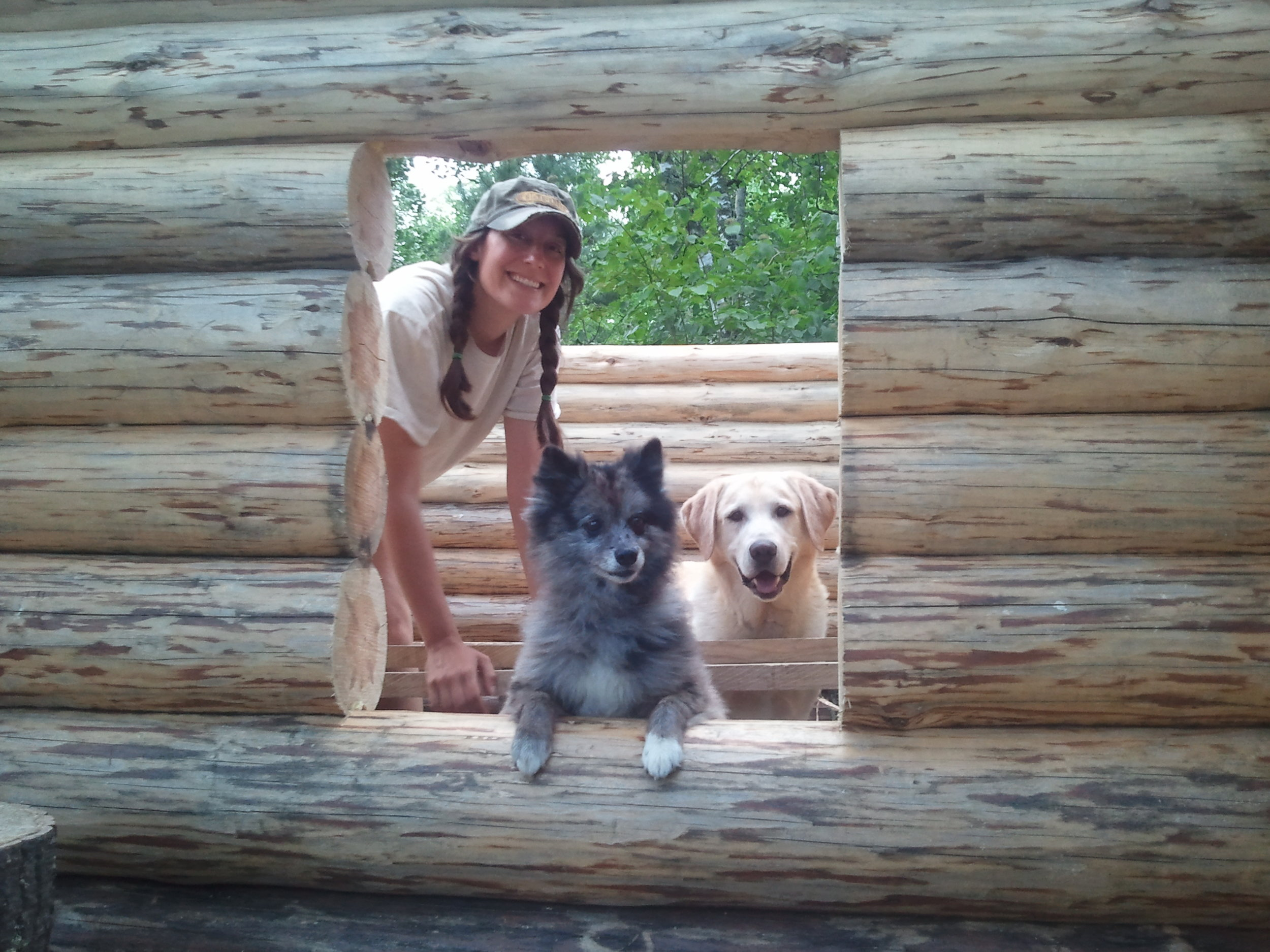 Ashlee with the hounds peaking out of our wilderness cabin.