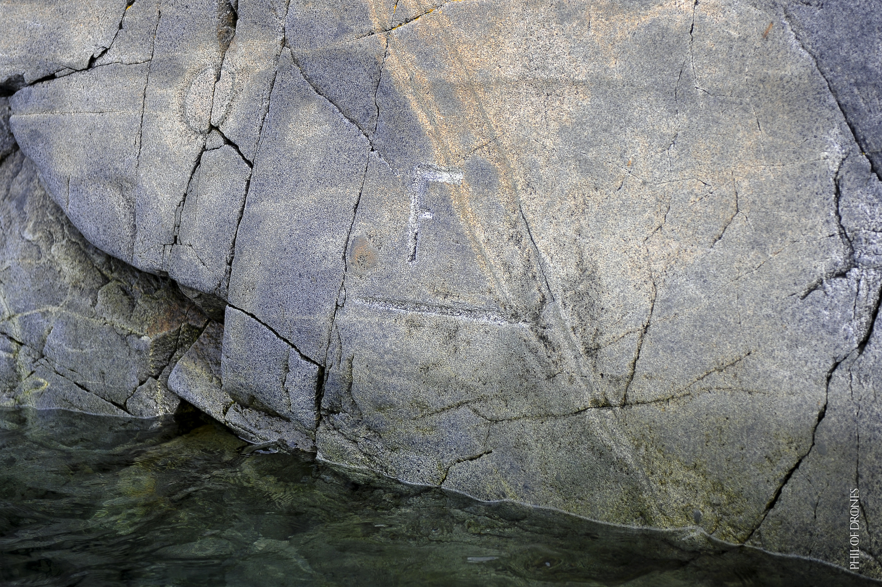 Le F du bateau le Français du Commandant Charcot gravé sur la roche dans la baie de Pléneau.