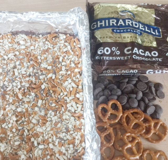 Ingredients for cookies and cookies layered in pan topped with crushed pretzels. Note the pretzels are various sizes.
