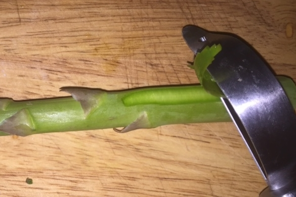 To peel, lay spear flat and run carrot peeler toward stem end. Turn and peel all the way around.