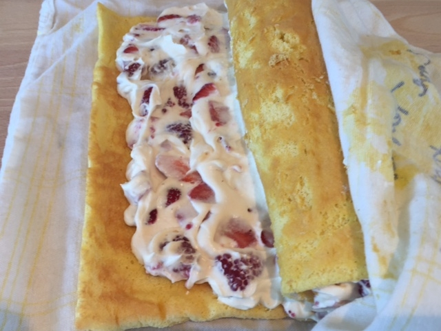 Using towel to help you,roll cake up around filling. Slide roll onto a sheet of heavy foil and place seam side down. Wrap in foil and refrigerate until chilled..