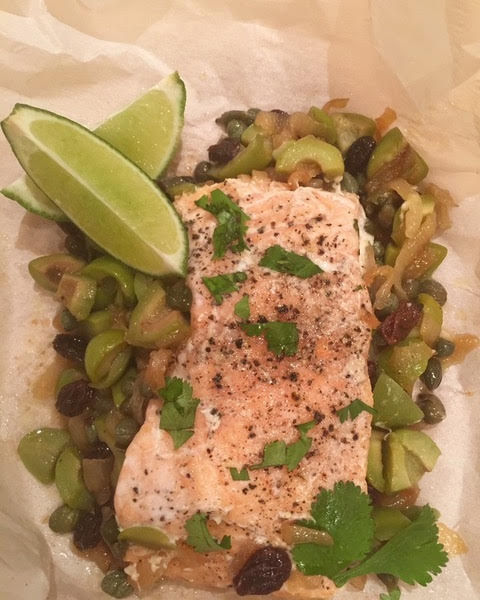 Cooked salmon baked in parchment on a green olive, caper,caramelized onion and raisin sauce.