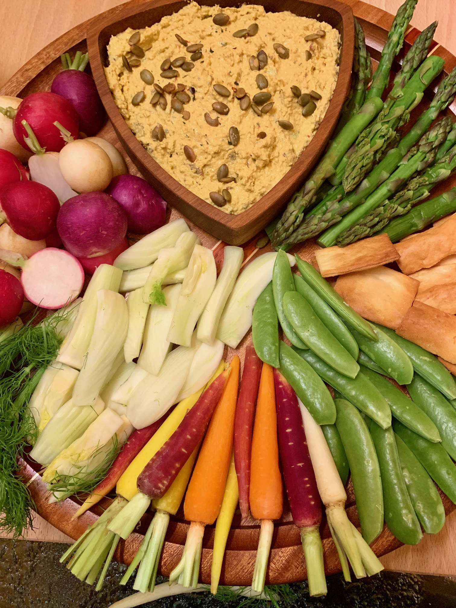 Serve with pita chips and assorted veggies. Pictured here rainbow radishes, fennel, rainbow carrots, sugar snap peas, pita chips and cooked asparagus.