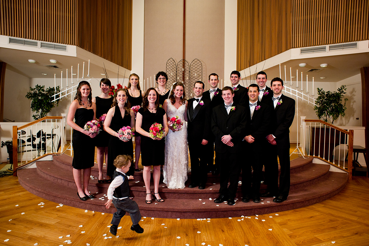 the ring bearer jumps across the wedding party portrait