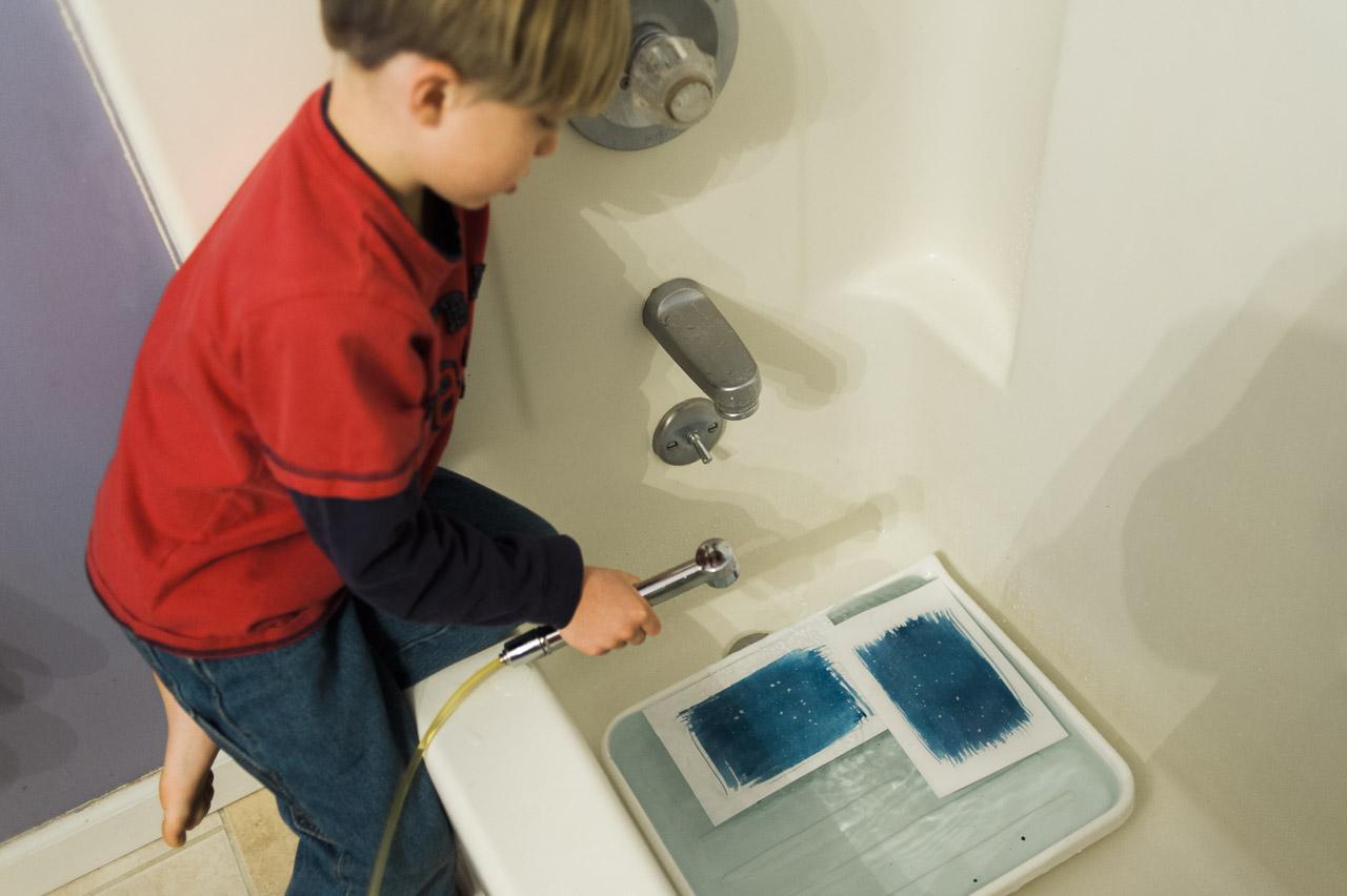 child helping rinse cyanotype prints / (c) jocelynmathewes.com