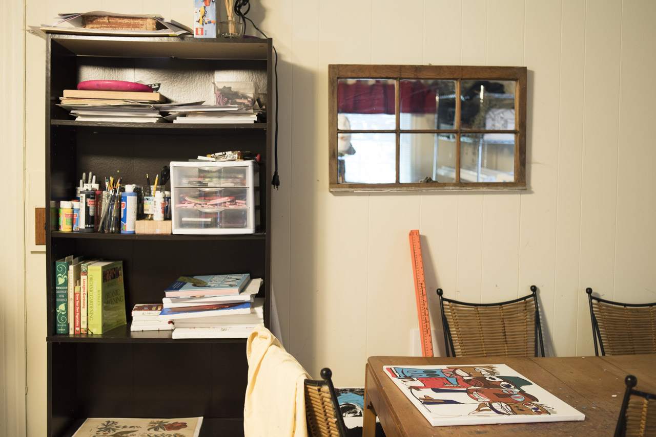 The workspace table & art supply shelves.