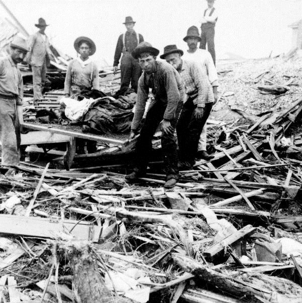 Survivors carry the dead out of the wreckage