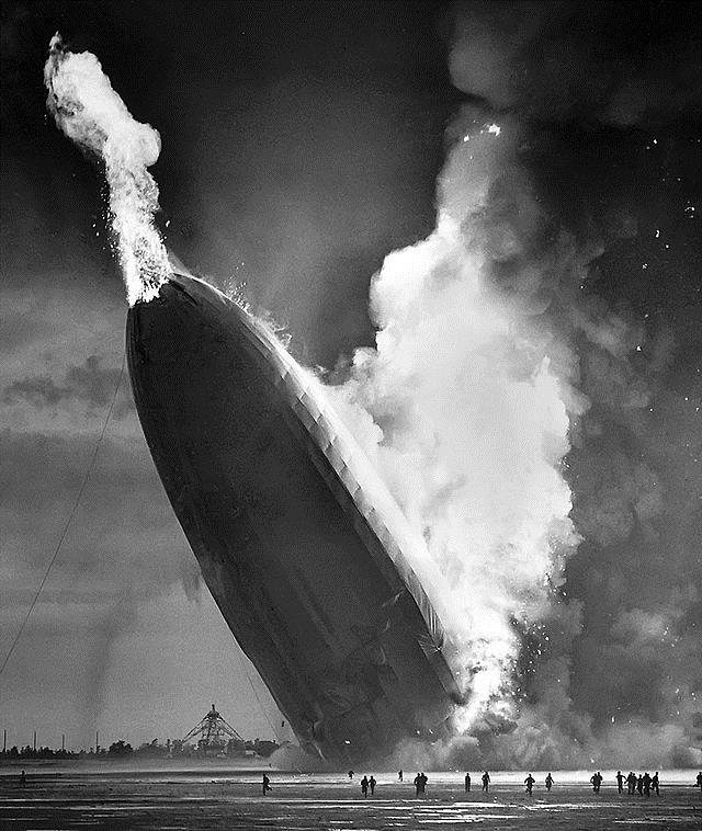 As the hydrogen gas burned and escaped from the rear of the Hindenburg, the tail dropped to the ground sending a burst of flame punching through the nose. The ground crew below scatters to flee the inferno (photo courtesy AP)