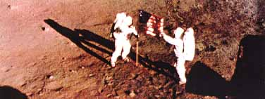 Neil Armstrong and Buzz Aldrin unfurl U.S. flag on Moon and are photographed by automatic camera in the Lunar Module window