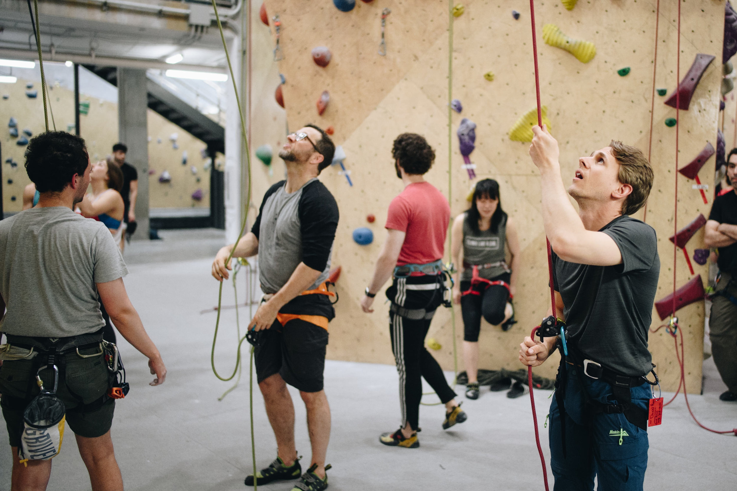Members of the  NYC Indoor Rock Climbing Newbies!  group take turns climbing and spotting.