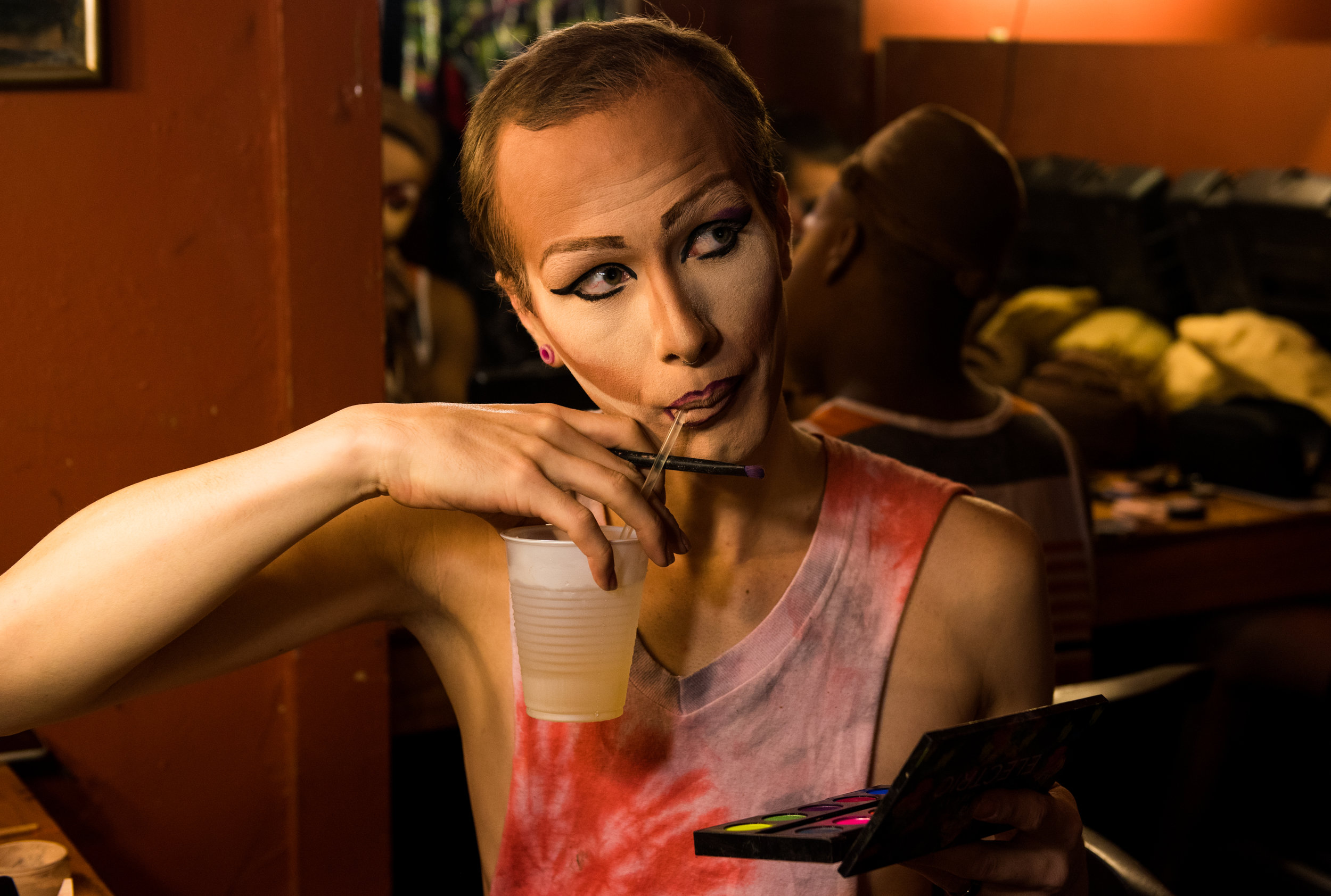 Looking up at another queen, Koedam pauses his eyeshadow application to take a sip of his drink.