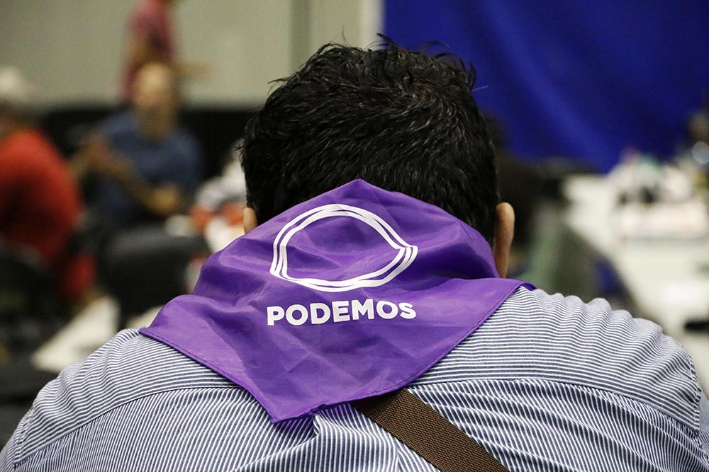 Un militante de Podemos espera por los resultados tras la jornada electoral brandeada como 26-J por la prensa local.