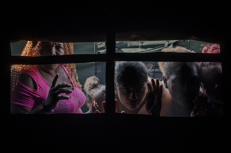 Vecinas miran a los damnificados dentro de las carpas colocadas en una calle de la Isla Trinitaria en Guayaquil tras un desalojo.