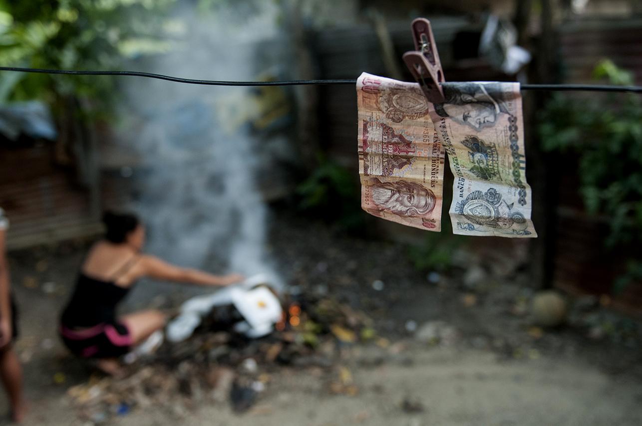 15 lempiras (0,5$) secándose en el tendedero mientras Artemis quema unos envases de comida china después de comer. Los billetes están mojados después de que los adolescentes jugaran a una batalla campal de baldes de agua.