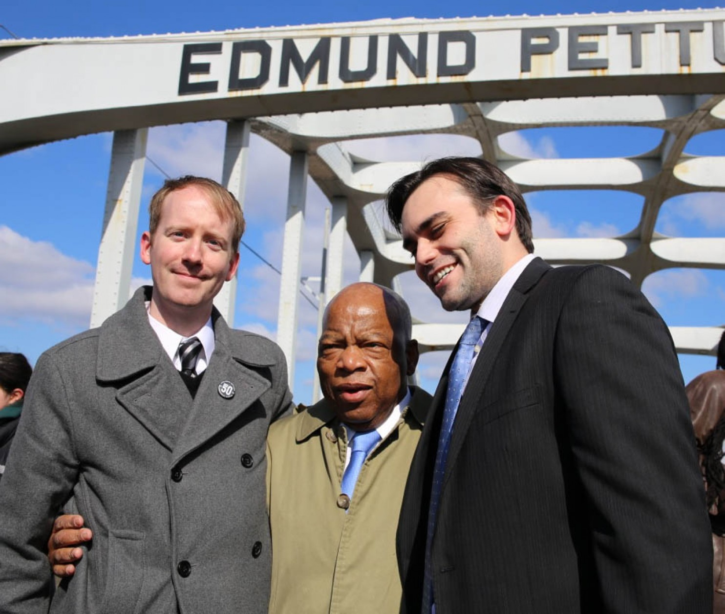 Authors Nate Powell, Rep. John Lewis and Andrew Aydin stand near the symbolic Edmund Pettus Bridge near Selma, Alabama.