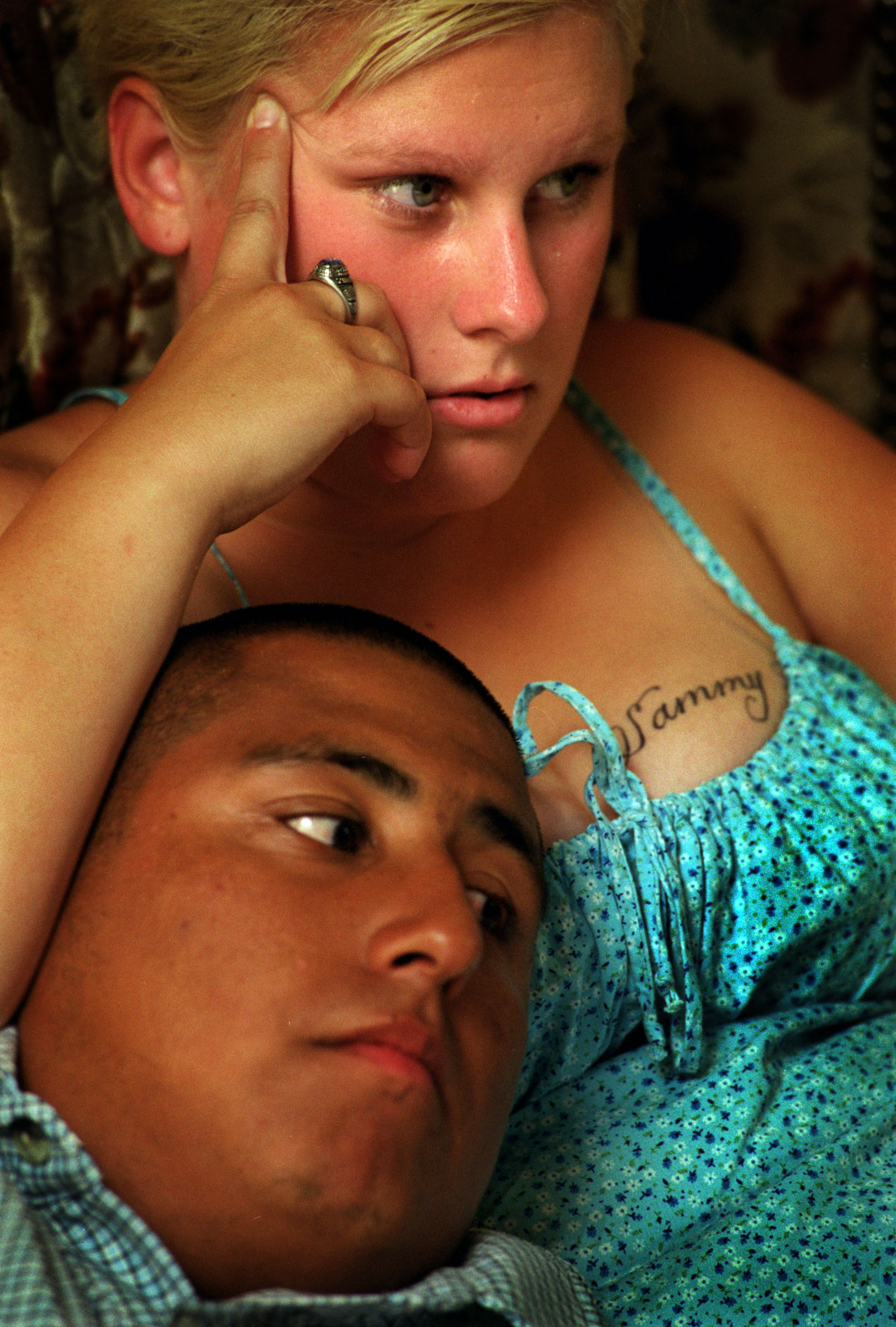 On her wedding night, Janea took Sam's name, Lopez, spending a quiet evening watching television.  Sam 19, weighs 300 pounds and loves telling tales of being a triggerman for LA's notorious Main Street Mafia. She has his name, Sammy, tattooed across her chest. ©Gail Fisher Los Angeles Times