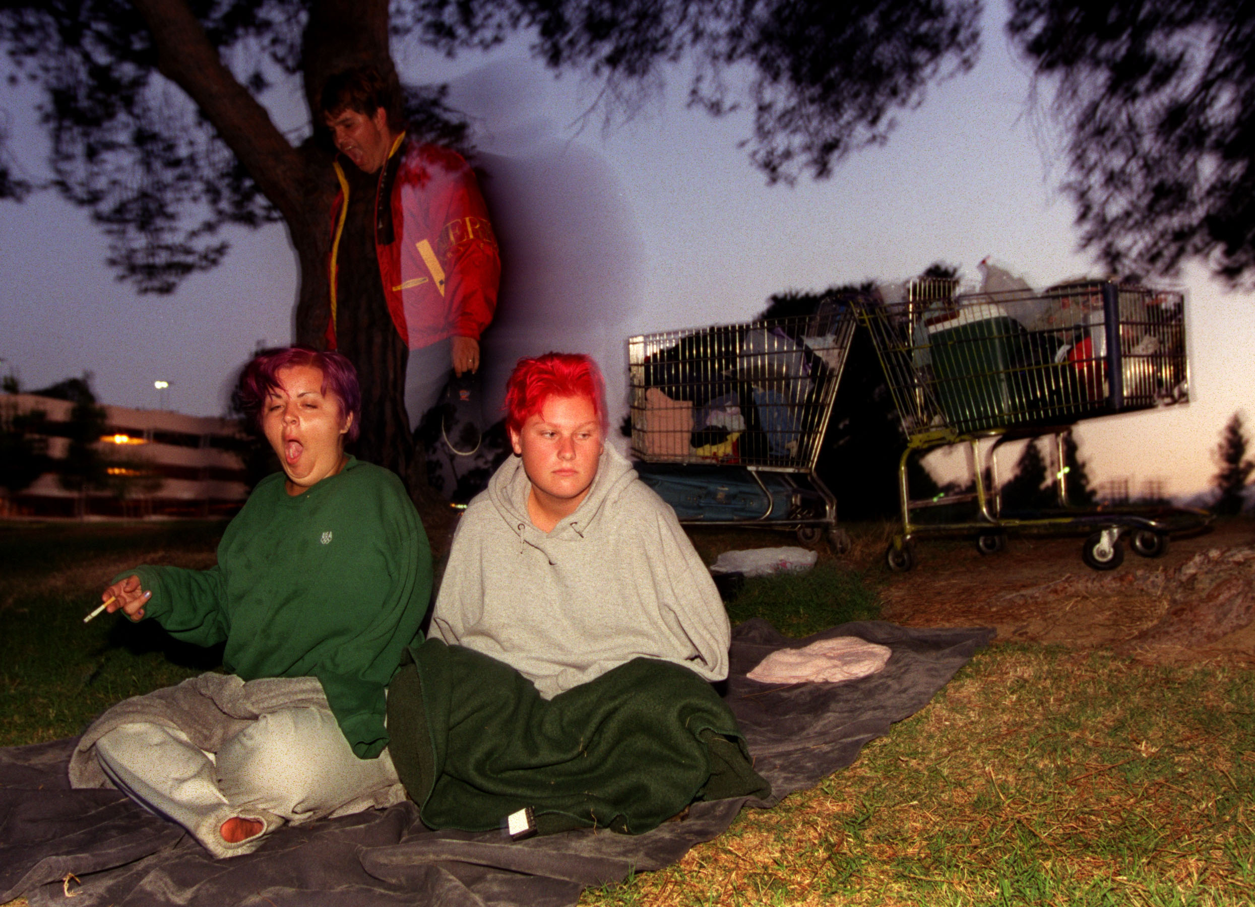 Wrapped in sweatshirts and blankets against the cool summer morning, Janea right, and her friends Dianna and Matt Dewey adjust to their new home with amazing ease. Wedged between East LA's municipal court, the freeway and a Sheriff's station, Belvedere Park, located on a few grassy acres, is where they are squatting these days. ©Gail Fisher Los Angeles Times