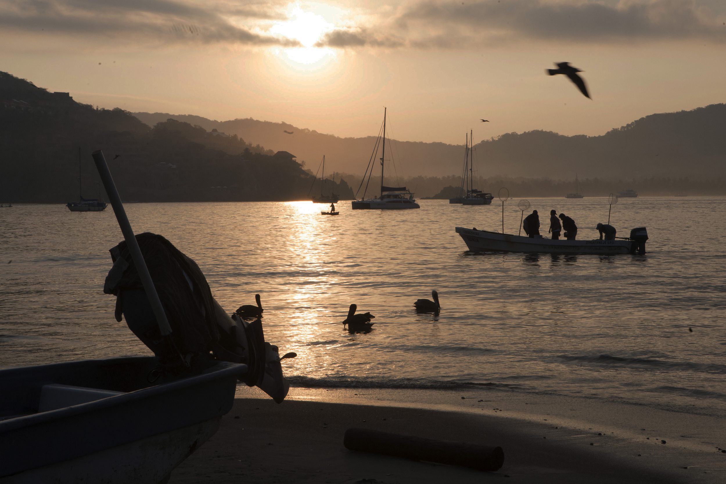 As the sun begins to rise over the calm bay, fishing boats return from a night's work to Playa Principal, the main beach in the center of town of Zihuatanejo. ©Gail Fisher