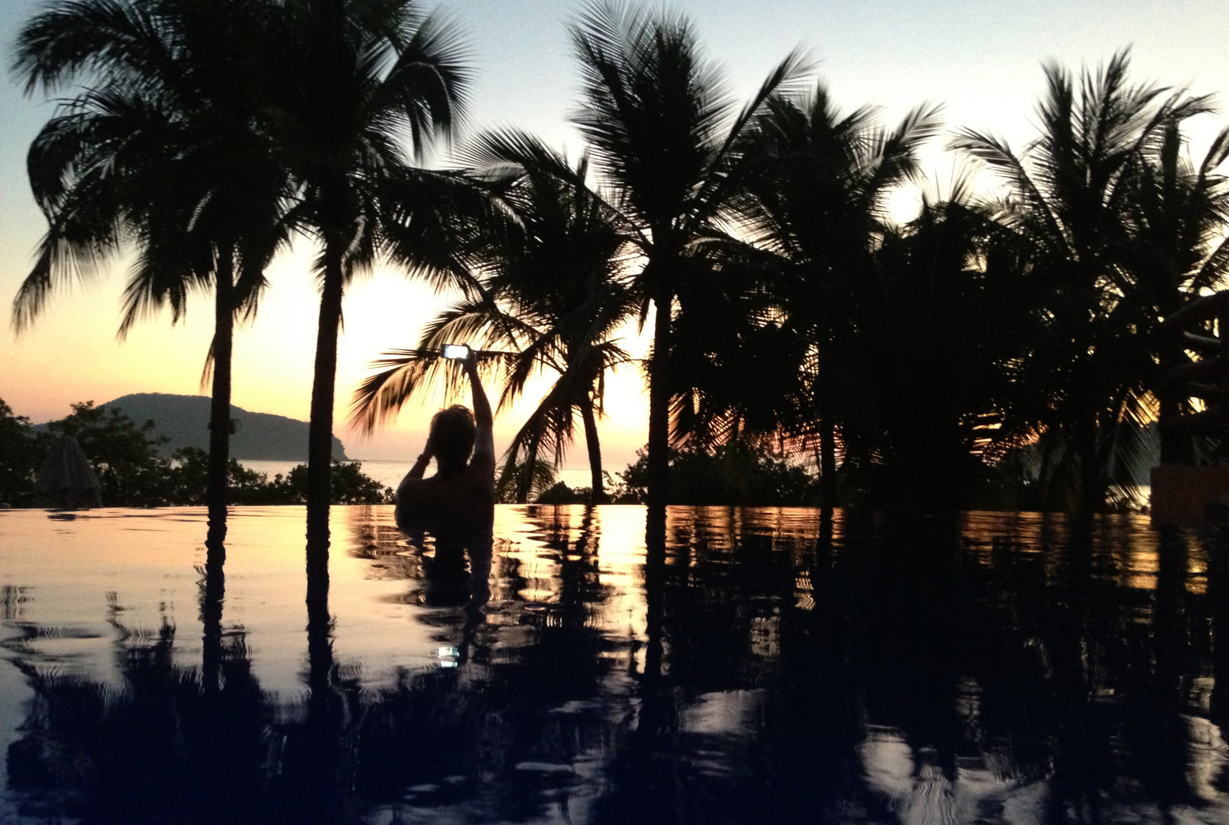 Reflecting palm fronds on a pool of tranquil blue and pink, the perspective plays tricks with one's mind.  Where the infinity pool at Club Intrawest ends, the sea begins, as dusk descends over Playa La Ropa in Zihuatanejo, Mexico. ©Gail Fisher