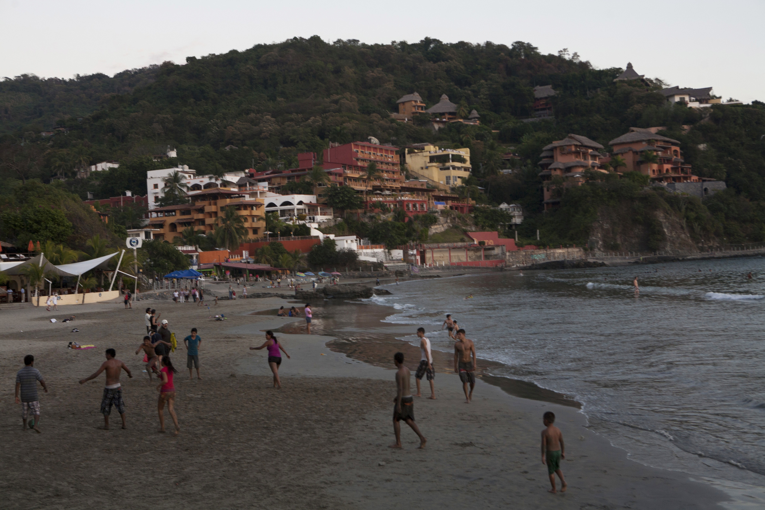 The locals enjoy an evening at Playa La Madera, (Wood Beach), a half mile stretch of sand where humble family eateries, restaurants, bungalows and hotels dot the cement and sand walkway. ©Gail Fisher