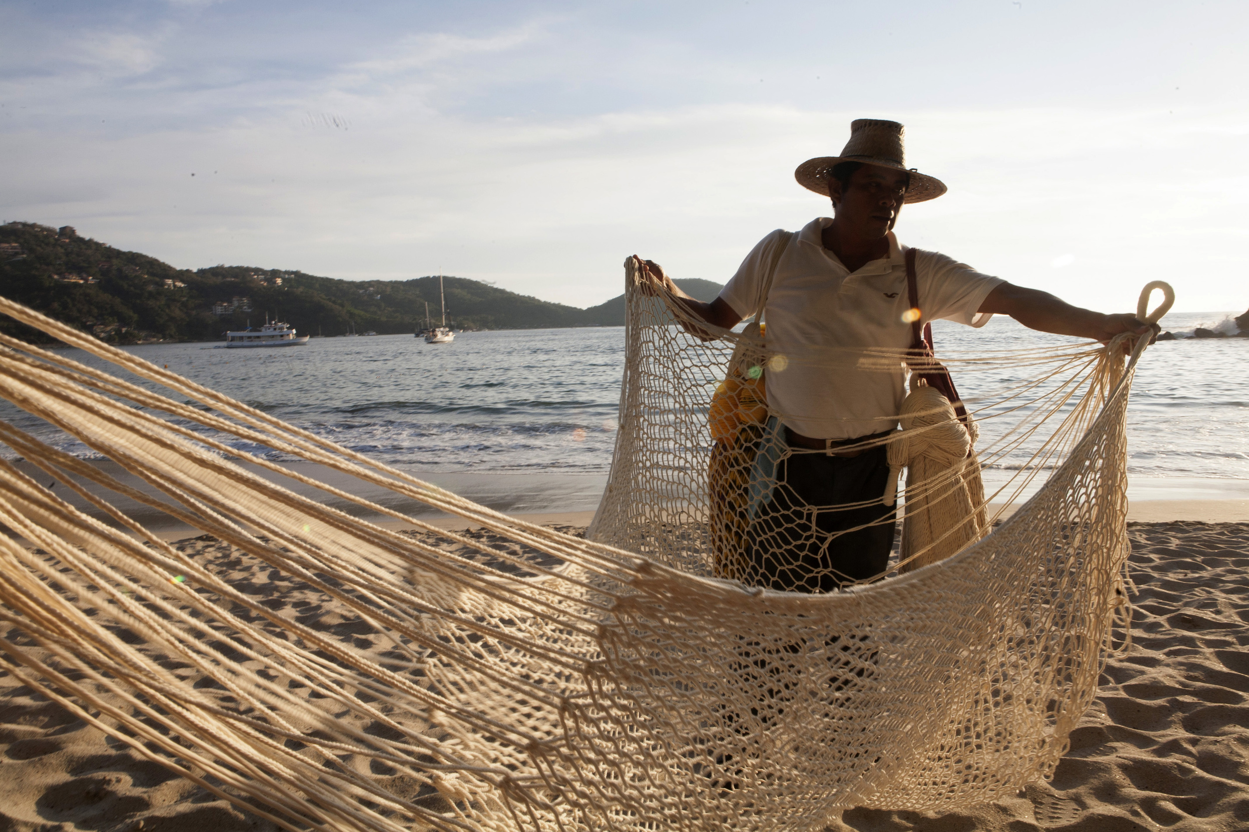 "Locals sell their wares including hammocks on Zihua's Playa La Ropa, or ""Clothing Beach."" According to legend, the beach got it's name when a Chinese textile ship crashed and spilled it's silks which washed up on the sand. ©Gail Fisher"