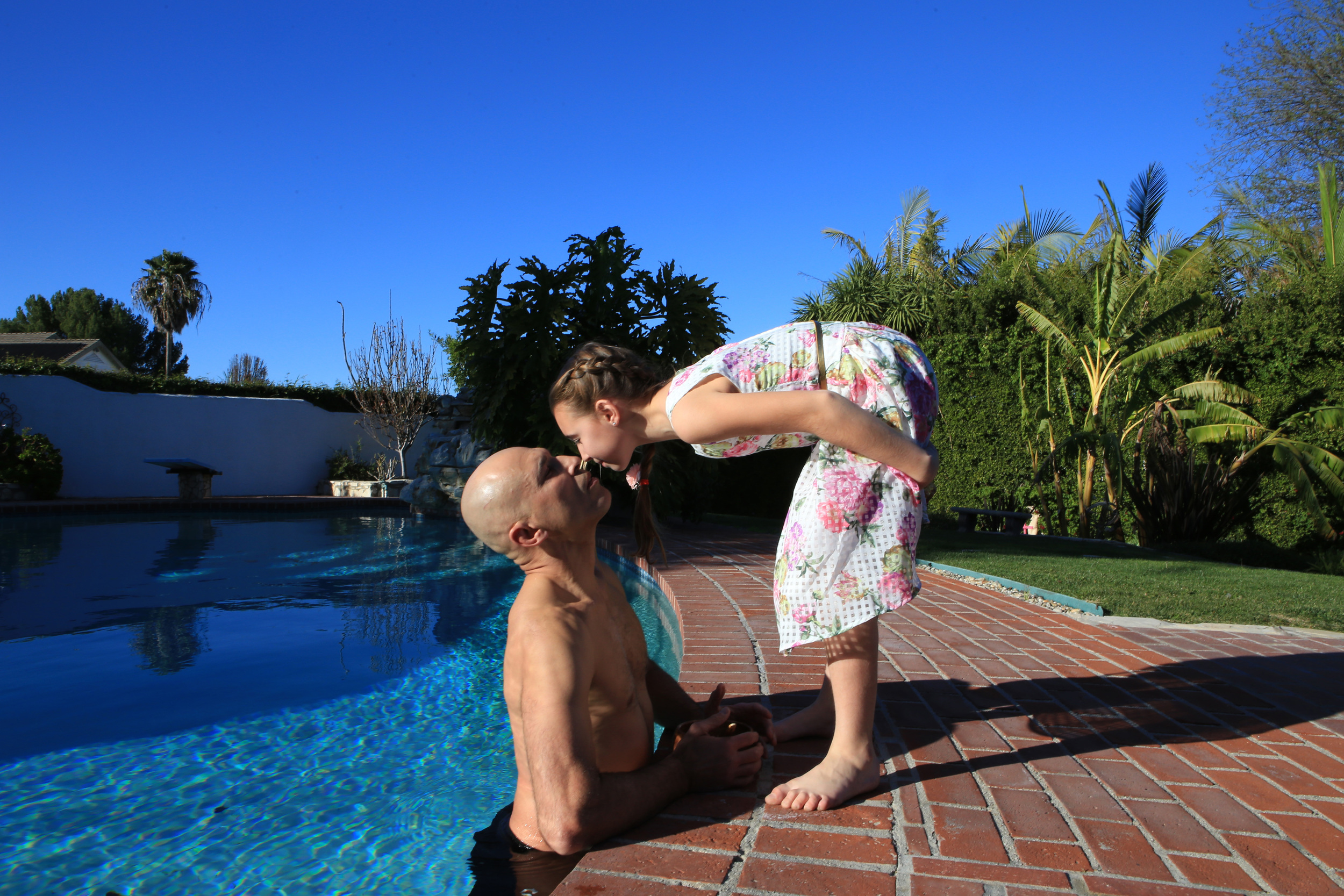 At his home in Palos Verdes Estates, CA, Gracie stands up to his waist for several minutes icing his legs and spine in their family pool after a strenuous day of training and sparing and is greeted by his 10-year-old daughter, Kharianna, who has just returned home from school and music lessons. (©Gail Fisher for ESPN)