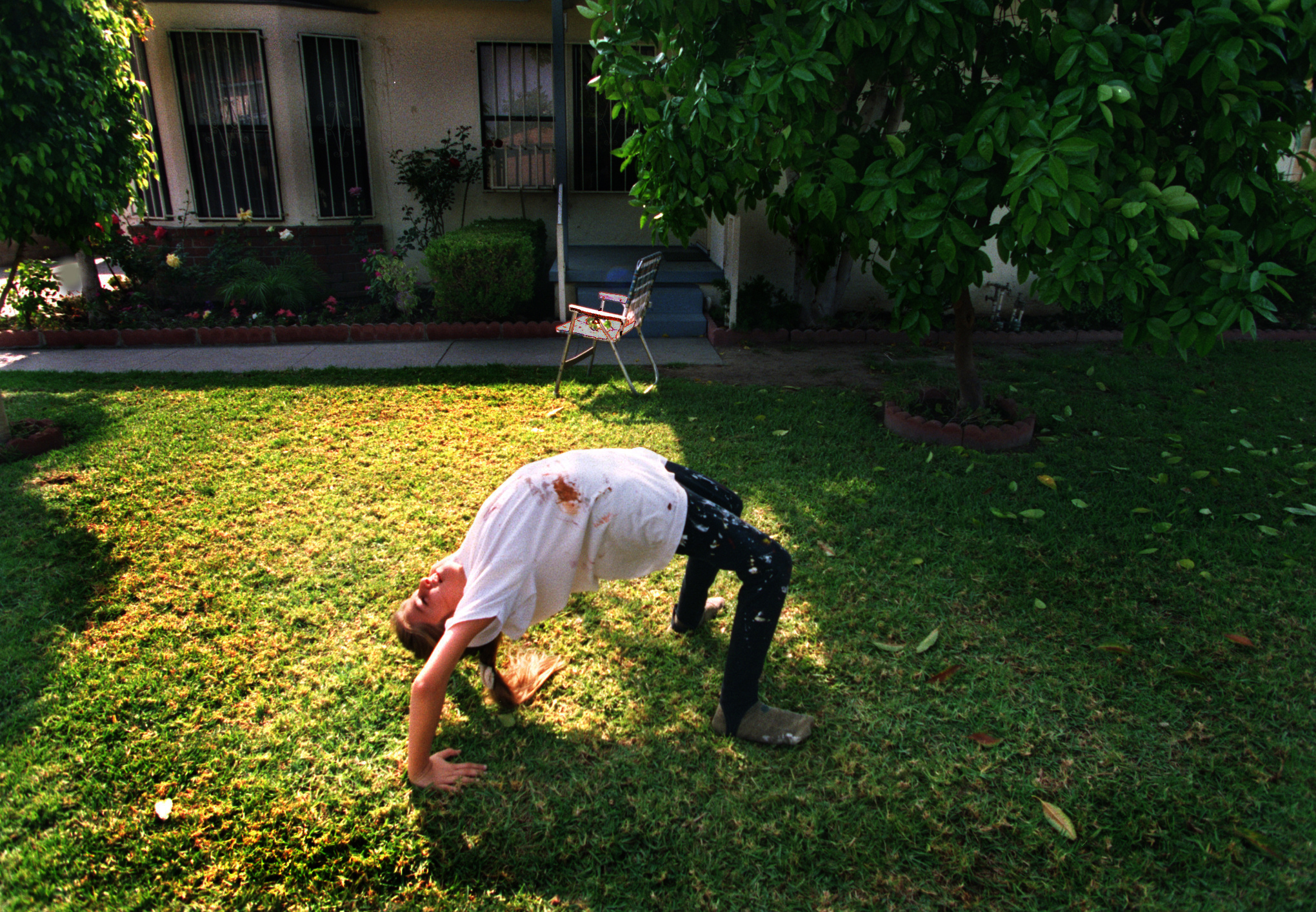 Alexandra Nechita takes a diversion from painting by turning cartwheels in the front yard of their Norwalk home. Only a wall separates their backyard from the Interstate 5. Her agent in Costa Mesa says if it were up to him, he'd move the family tomorrow, that the neighborhood worries him sick. ©Gail Fisher Los Angeles Times