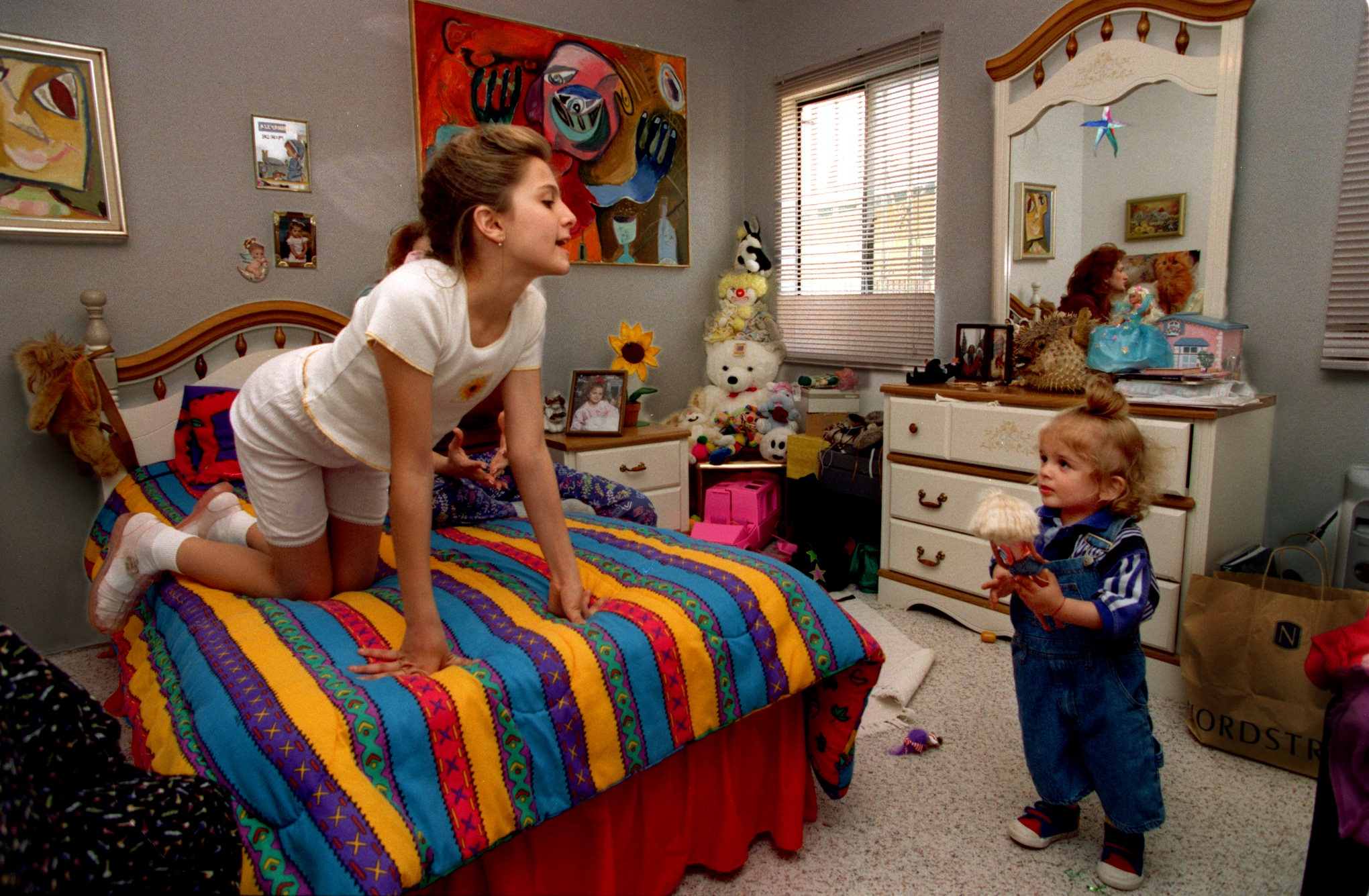 Alexandra Nechita sprawled out on her Pocahontas bedspread in her Norwalk home, playing with Maximillian. She says that aside from painting, she likes nothing better than playing with her baby brother, her best friend. ©Gail Fisher Los Angeles Times