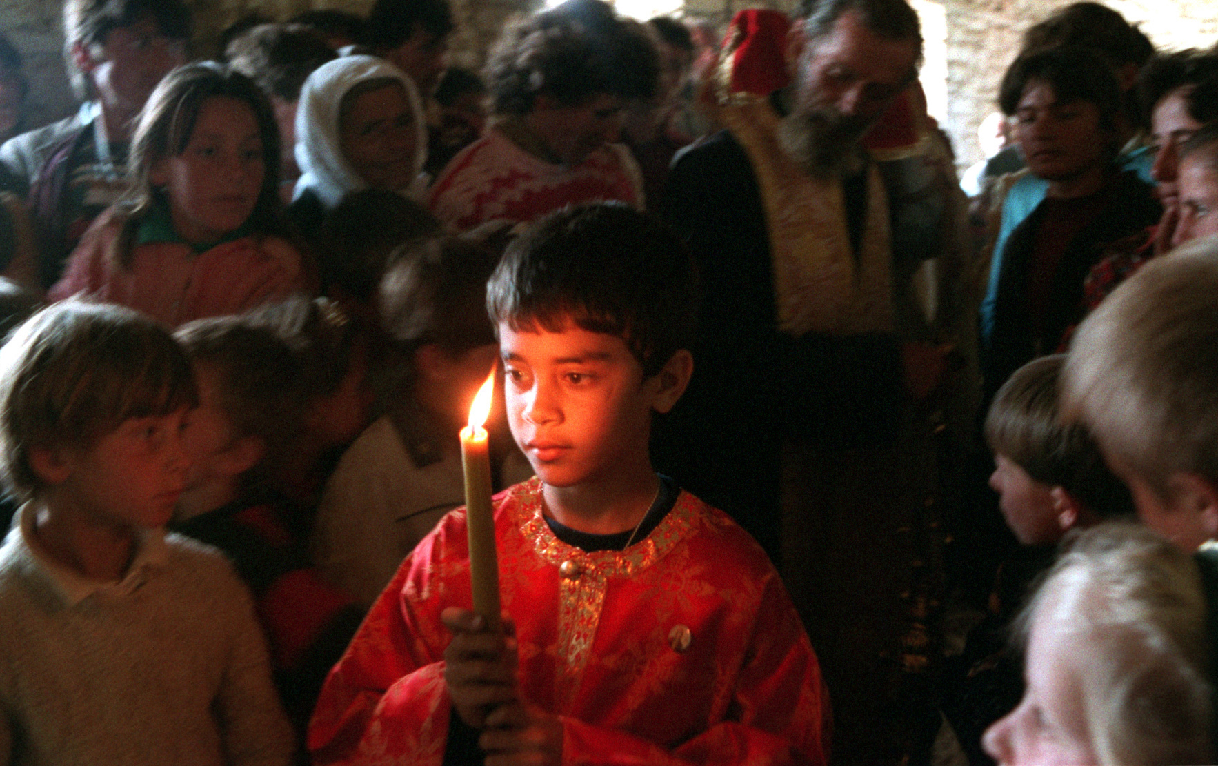 Stephanos Ritsi, 9, son of Father Martin Ritsi, helps with the liturgy at St. Martin's Church in the village of Jeronisht. Ritsi has been helping to resurrect religion in long-isolated Albania. ©Gail Fisher Los Angeles Times